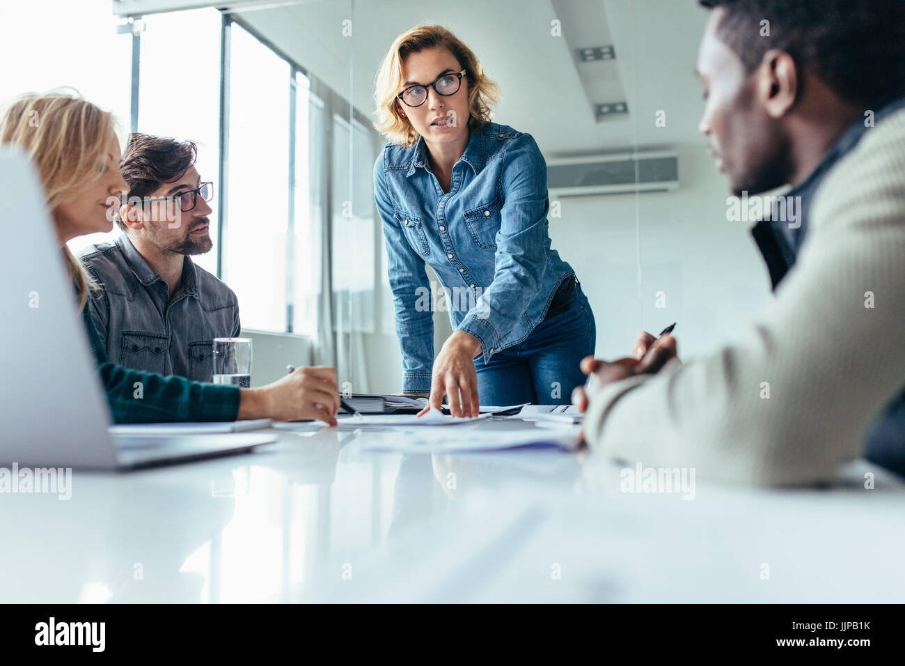 Businesswoman standing and leading business presentation. Female executive putting her ideas during presentation - Stock Image