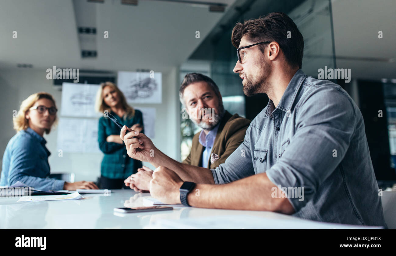 Young designer giving some new ideas about project to his partners in conference room. Business people discussing - Stock Image