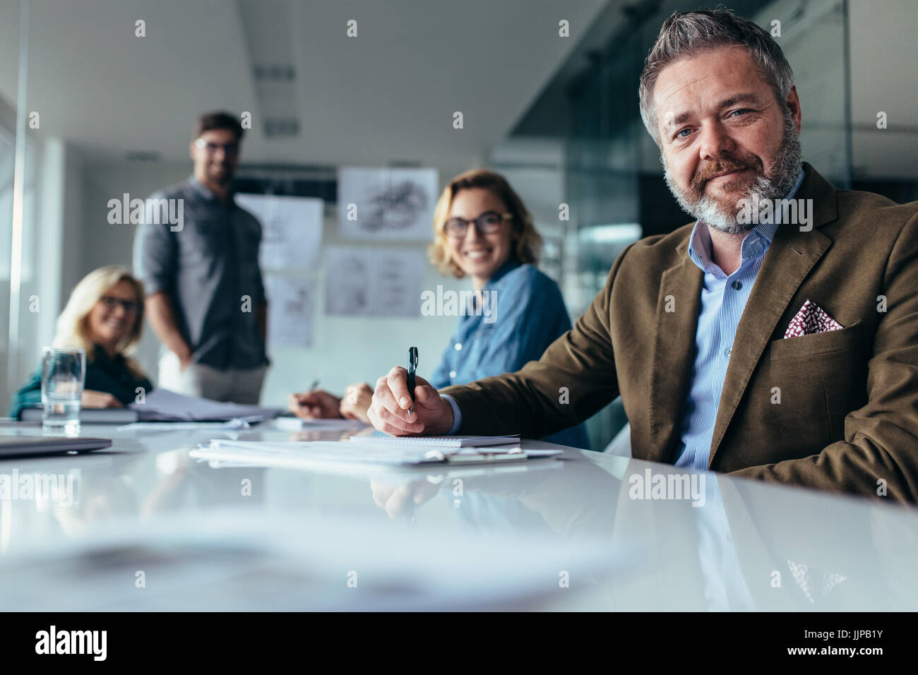 Businesspeople looking at camera with smile. Team of professionals sitting in boardroom. - Stock Image