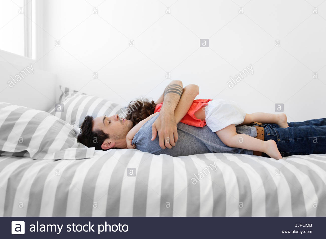 Man wearing grey T-shirt and jeans lying on bed with stripy duvet, hugging baby girl in red dress. - Stock Image