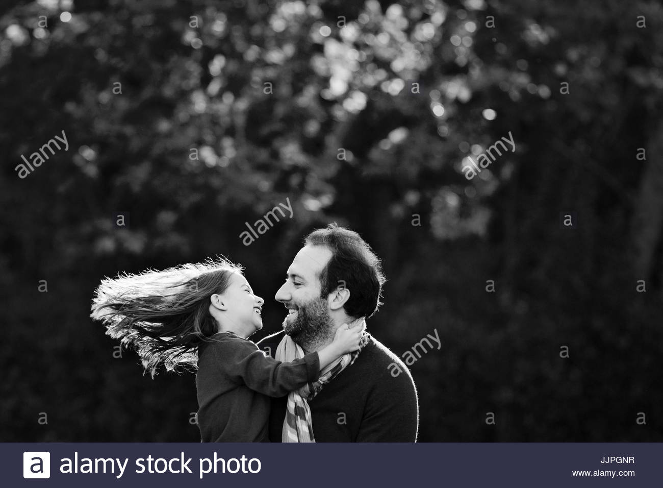 Smiling bearded man with girl in his arms, looking at each other, standing outdoors. - Stock Image