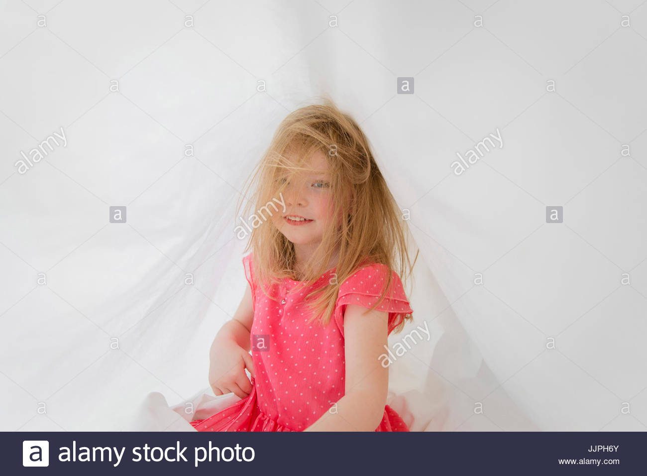 Smiling blond girl wearing red dress sitting on bed, tousled hair. - Stock Image