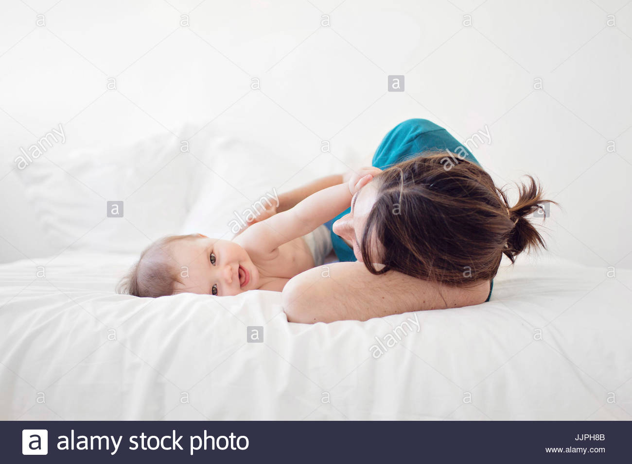 Woman wearing blue top and baby girl lying on a bed, smiling at camera. - Stock Image