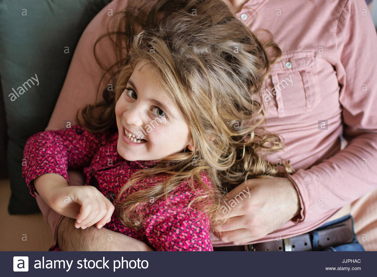 High angle view of smiling girl with tousled brown hair sitting on a mans lap. - Stock Image