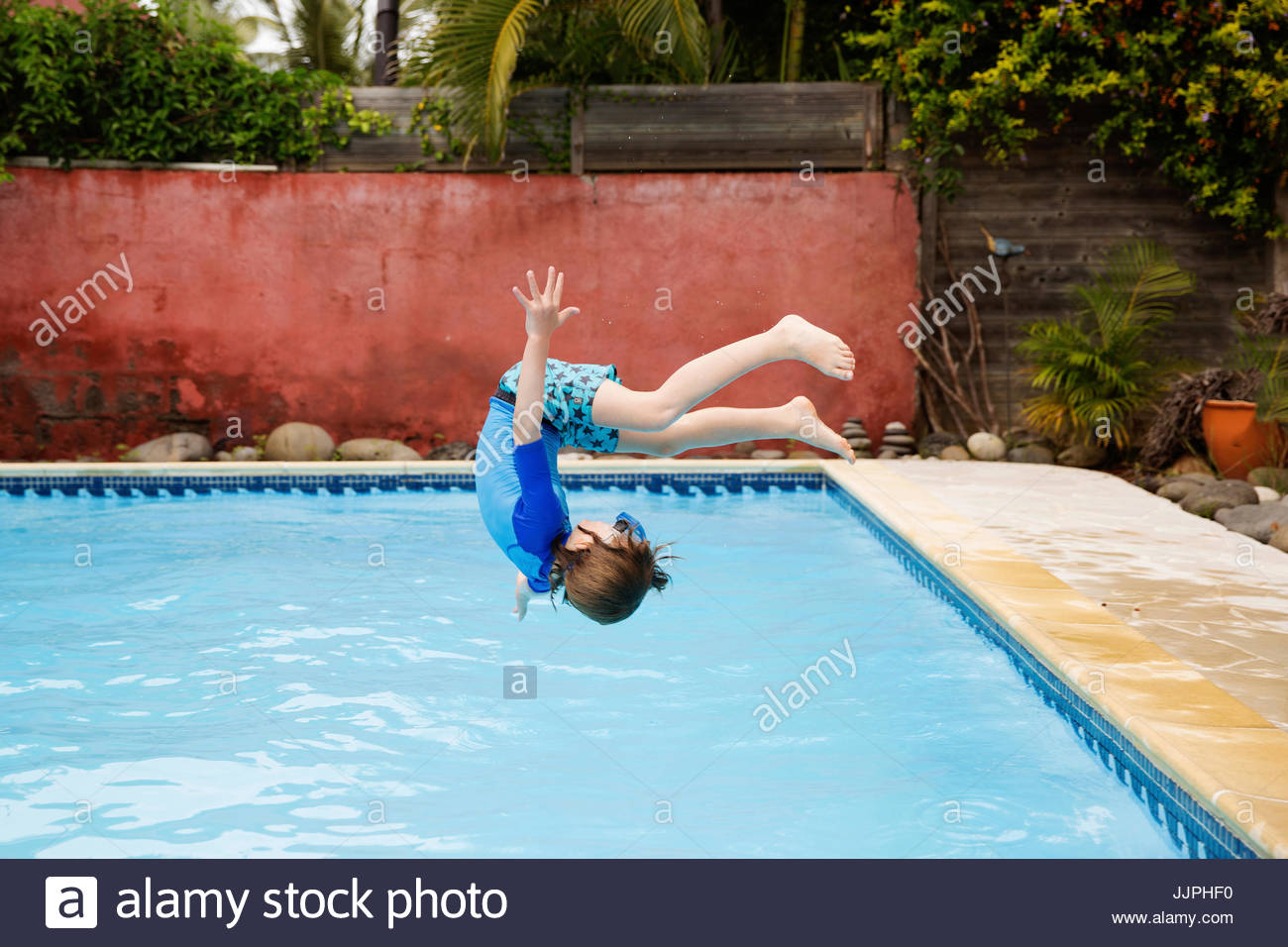 A boy in swim shorts, ten year old boy doing a back flip, a backwards somersault, into a swimming pool. - Stock Image
