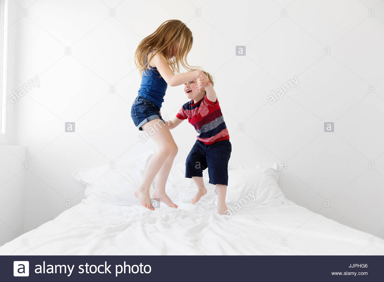 A six year old girl and four year old boy, brother and sister jumping up and down on a double bed. - Stock Image