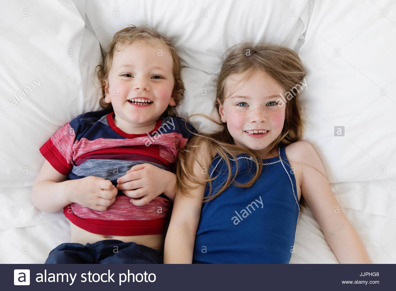 A six year old girl and four year old boy, brother and sister lying on a bed looking up at the camera. - Stock Image