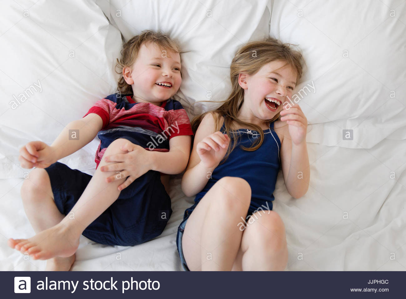 A six year old girl and four year old boy, brother and sister lying on a bed looking up at the camera, laughing. - Stock Image