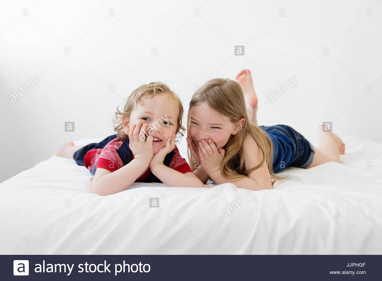 A six year old girl and four year old boy, brother and sister lying on a bed looking at the camera. - Stock Image