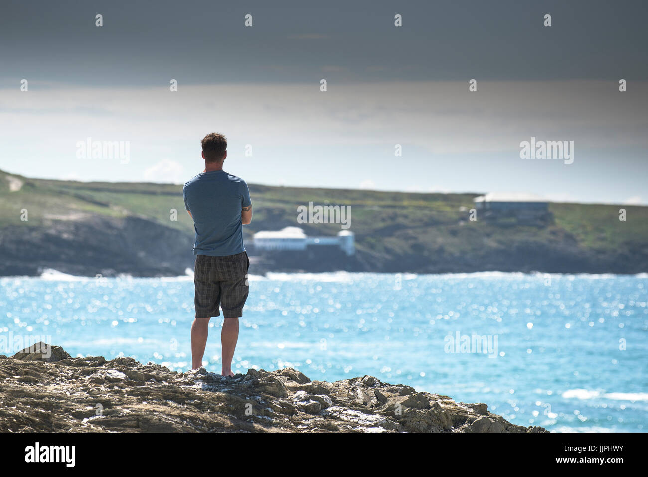 A holidaymaker stands on The Headland in Newquay looking out to sea. - Stock Image