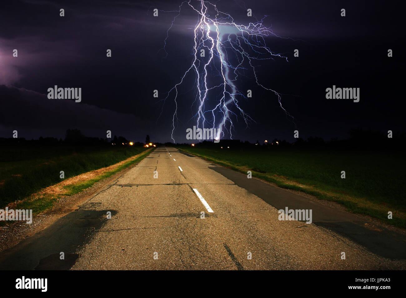 Lightning over asphalt road Stock Photo