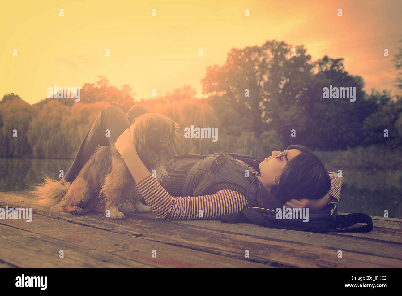 Vintage photo of relaxing woman with her dog on a pier Stock Photo