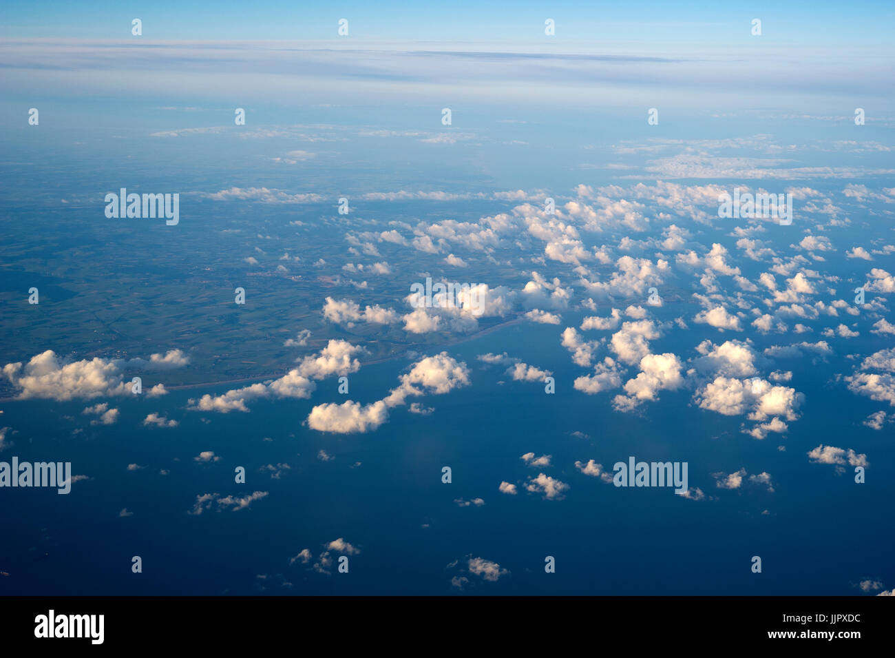 View of clouds in the sky and an ocean shore from an airplane window Stock Photo