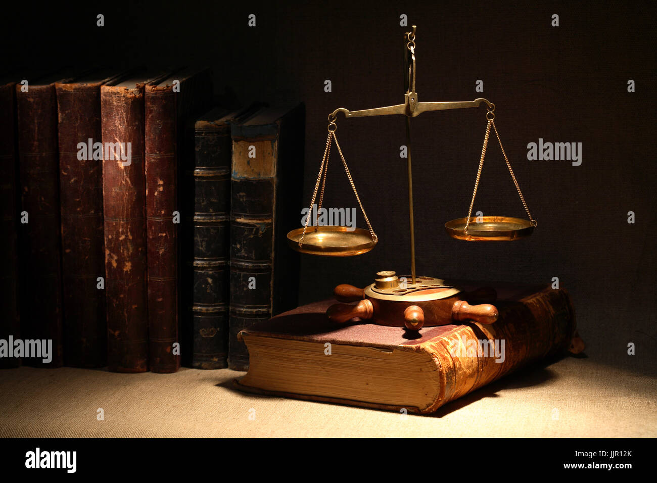 Legislation concept. Old brass weight scale and ancient books under beam of light on dark background - Stock Image