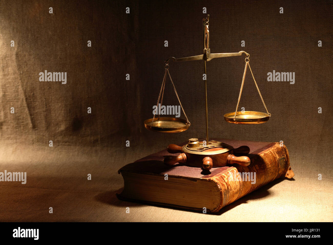Legislation concept. Old brass weight scale standing on ancient book under beam of light - Stock Image