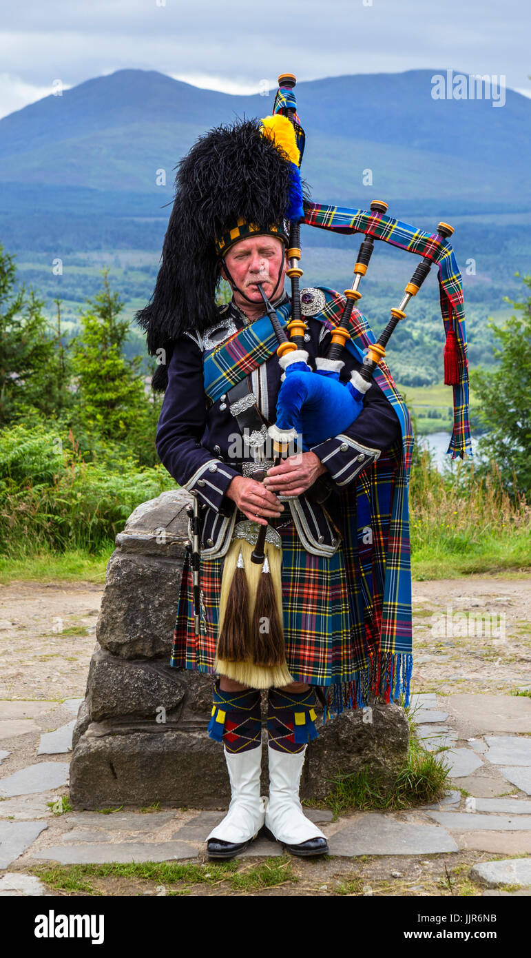 Traditional Scottish Piper playing the bagpipes at the Glen Garry viewpoint, Scottish Highlands, Scotland, UK - Stock Image