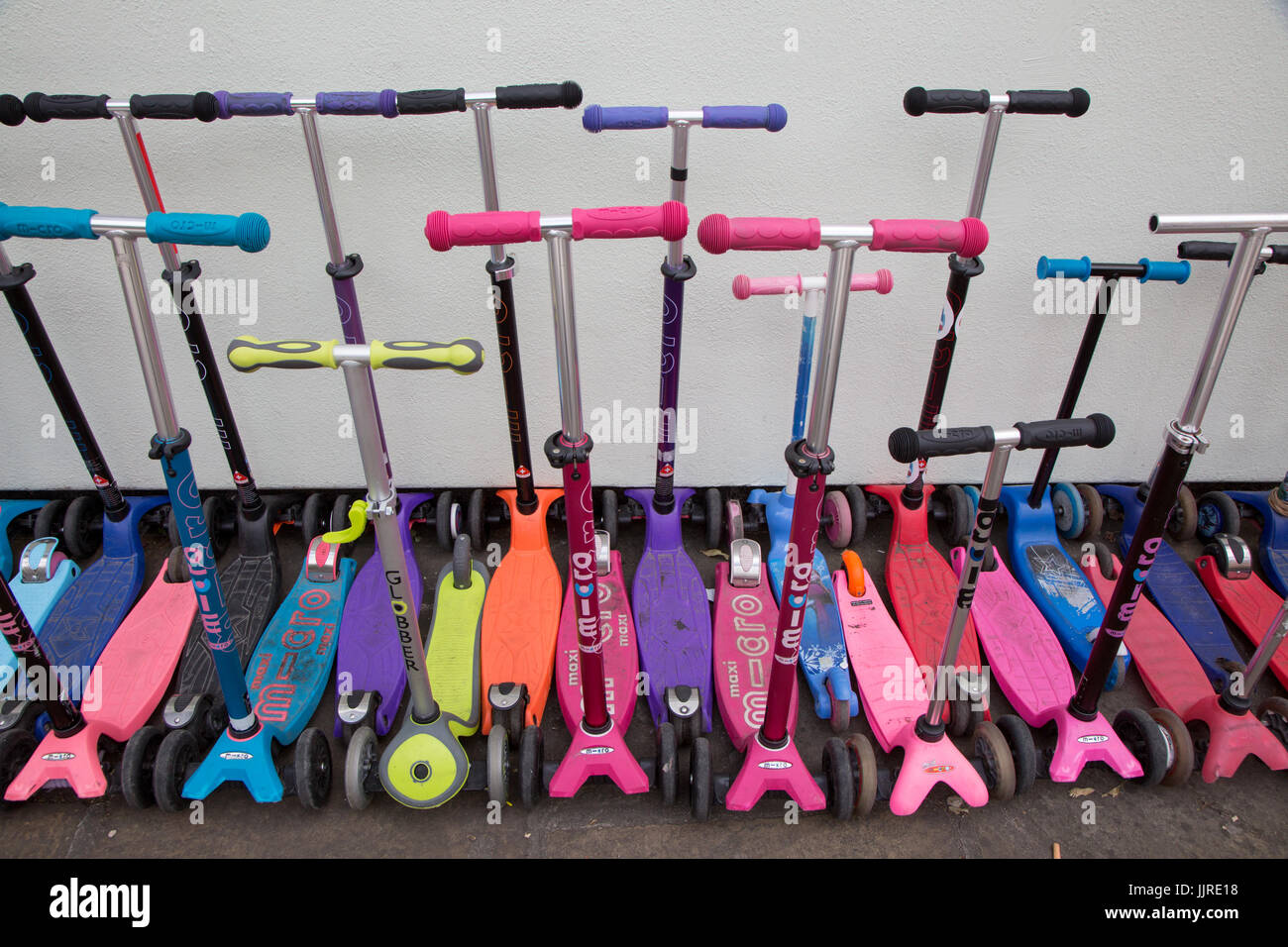 Scooters parked in a school playground in London - Stock Image