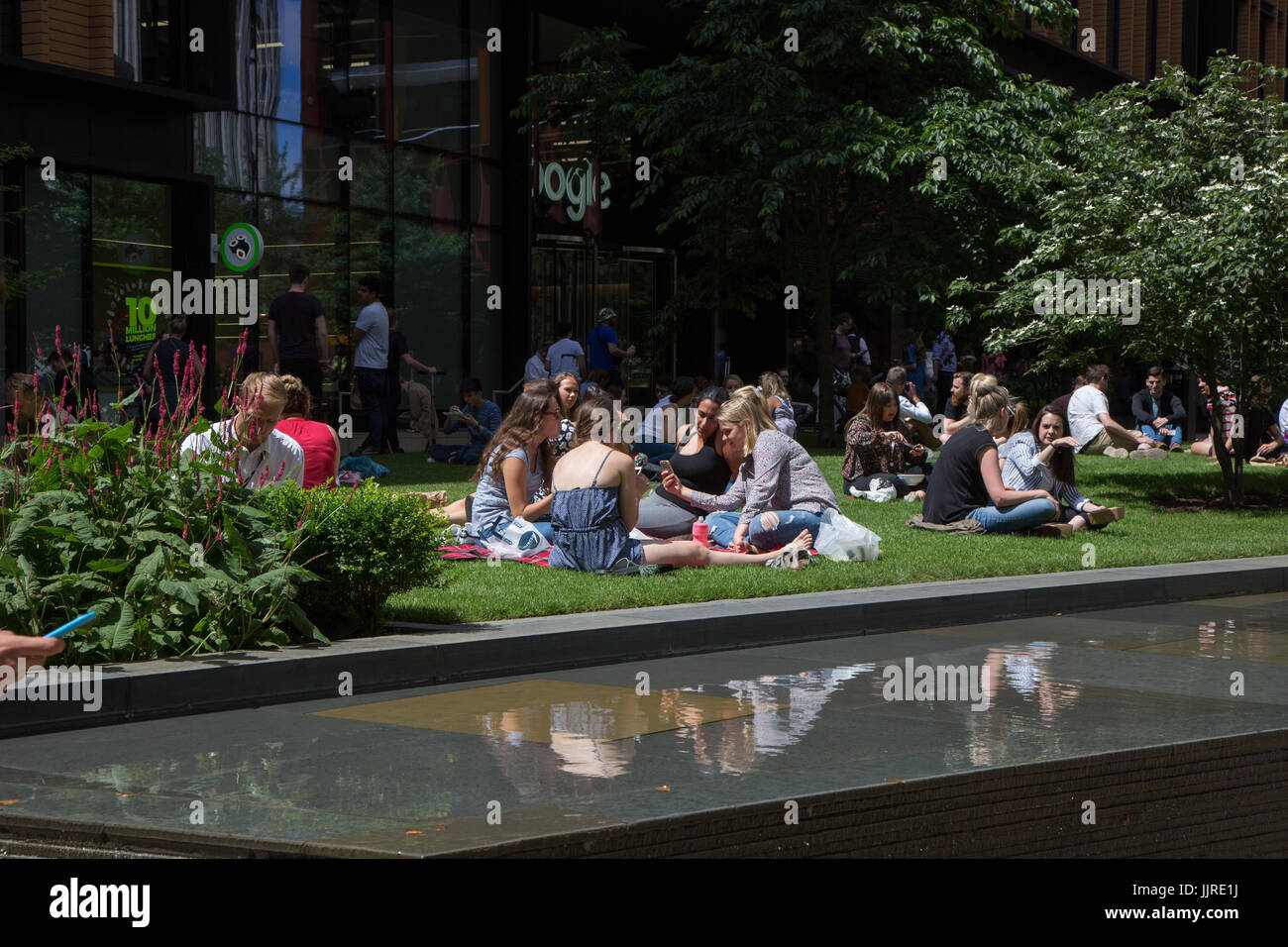 Employees from offices spill out for lunch on grass at Battle Bridge Place, Kings Cross - Stock Image