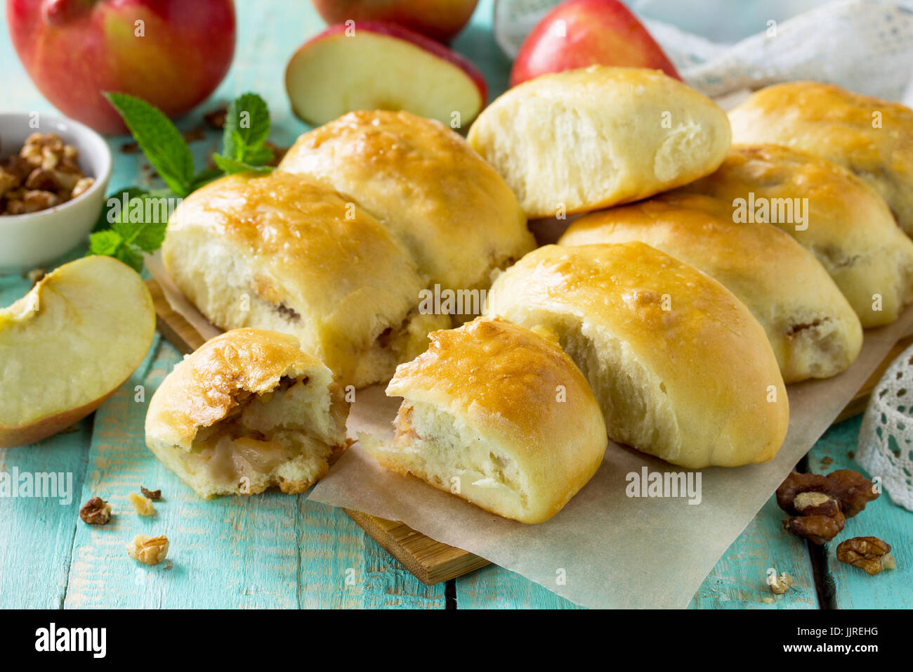 Homemade apple pies with fresh apples and walnuts from yeast dough on a kitchen wooden table. Apple patties on the - Stock Image