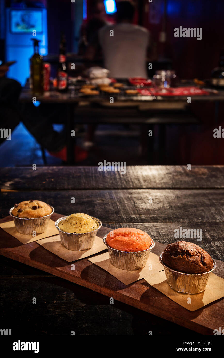 mixed freshly baked muffins on table in cozy coffeeshop interior - Stock Image