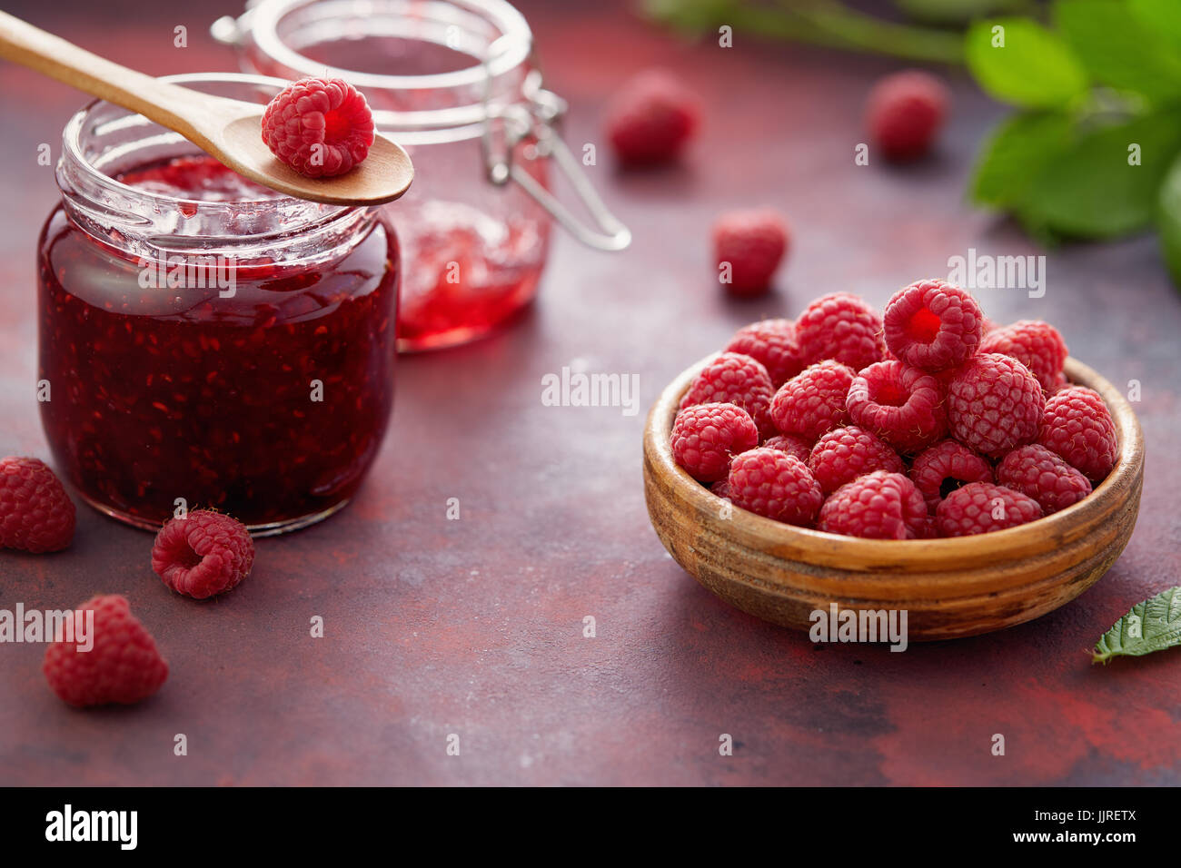Fresh raspberries and a jar of raspberry jam. - Stock Image