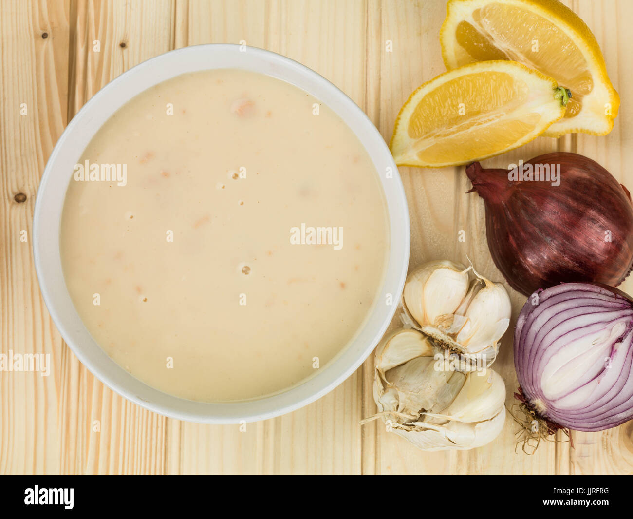 Bowl of Cream of Chicken Soup Against a Natural Wood Background - Stock Image