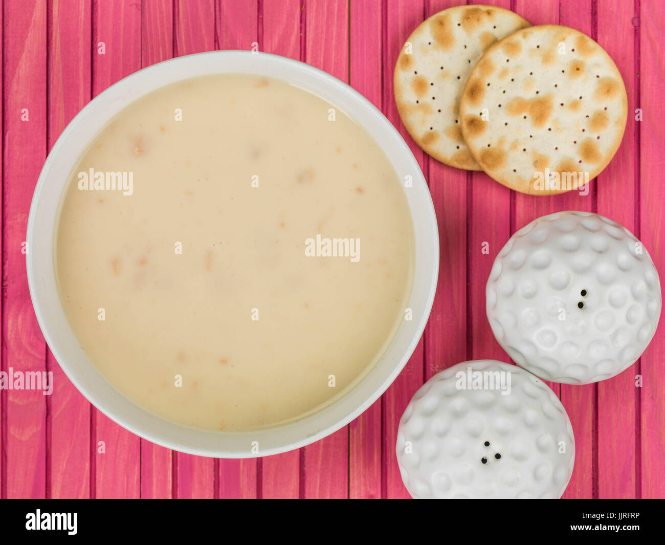 Bowl of Cream of Chicken Soup Against a Pink Wooden Background - Stock Image
