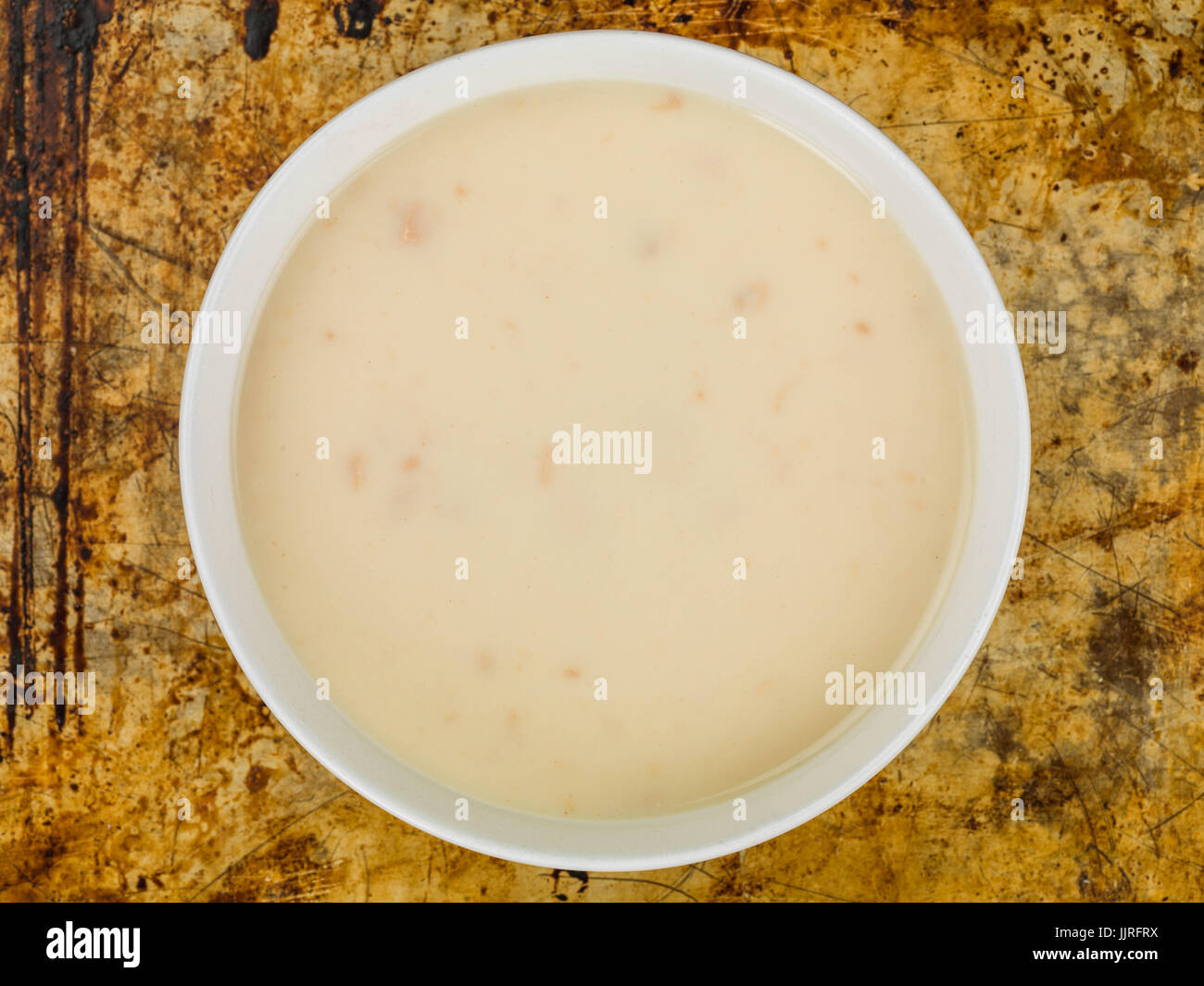 Bowl of Cream of Chicken Soup Against a Distressed Used Oven Tray - Stock Image