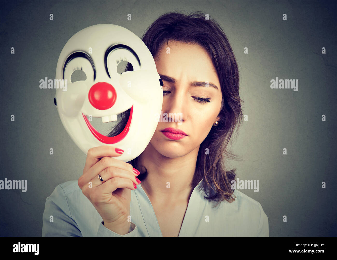 Portrait sad woman taking off happy clown mask isolated on gray wall background. Human emotions feelings - Stock Image