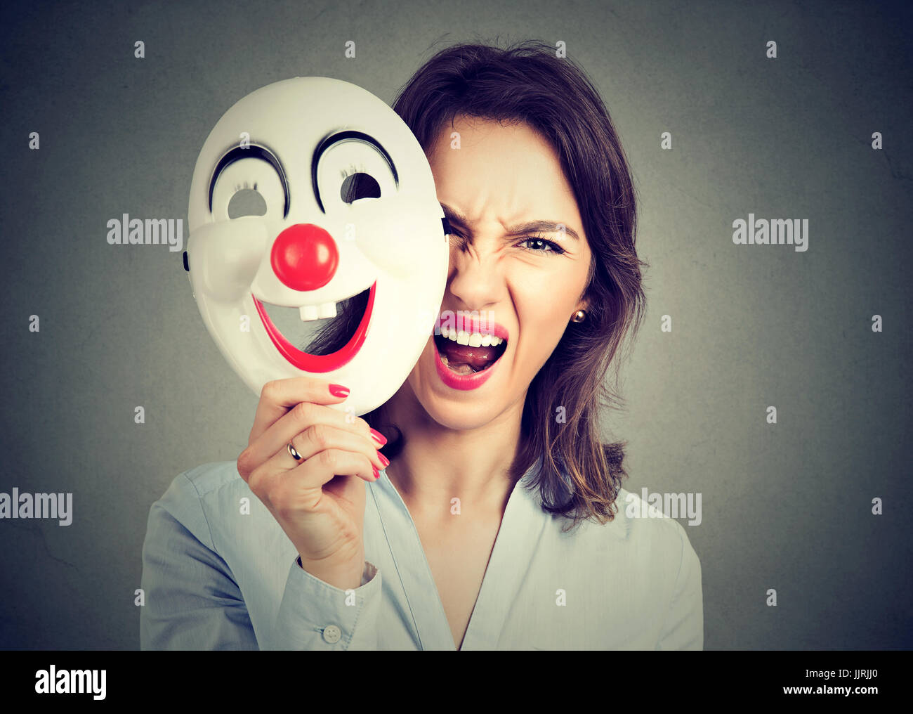 Portrait angry screaming woman taking off happy clown mask isolated on gray wall background. Negative human emotions - Stock Image