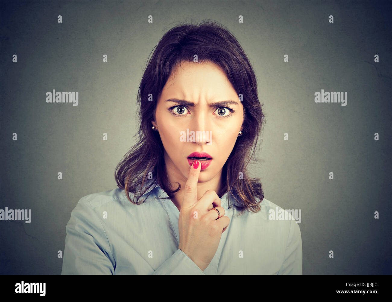 Surprised amazed scared woman looking at camera - Stock Image