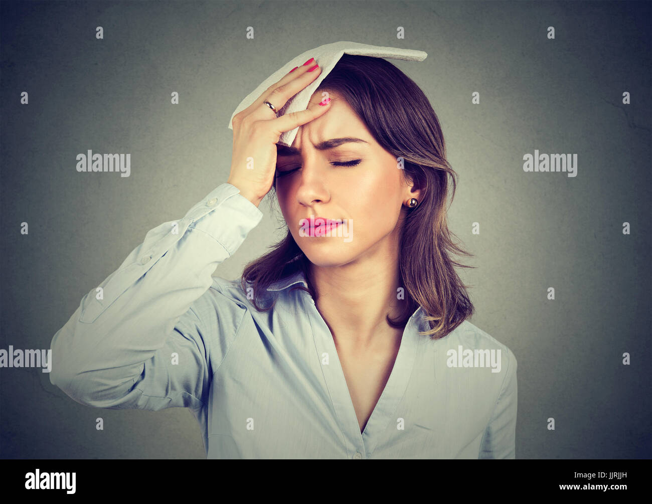 young woman wipes sweat from her forehead with a handkerchief - Stock Image