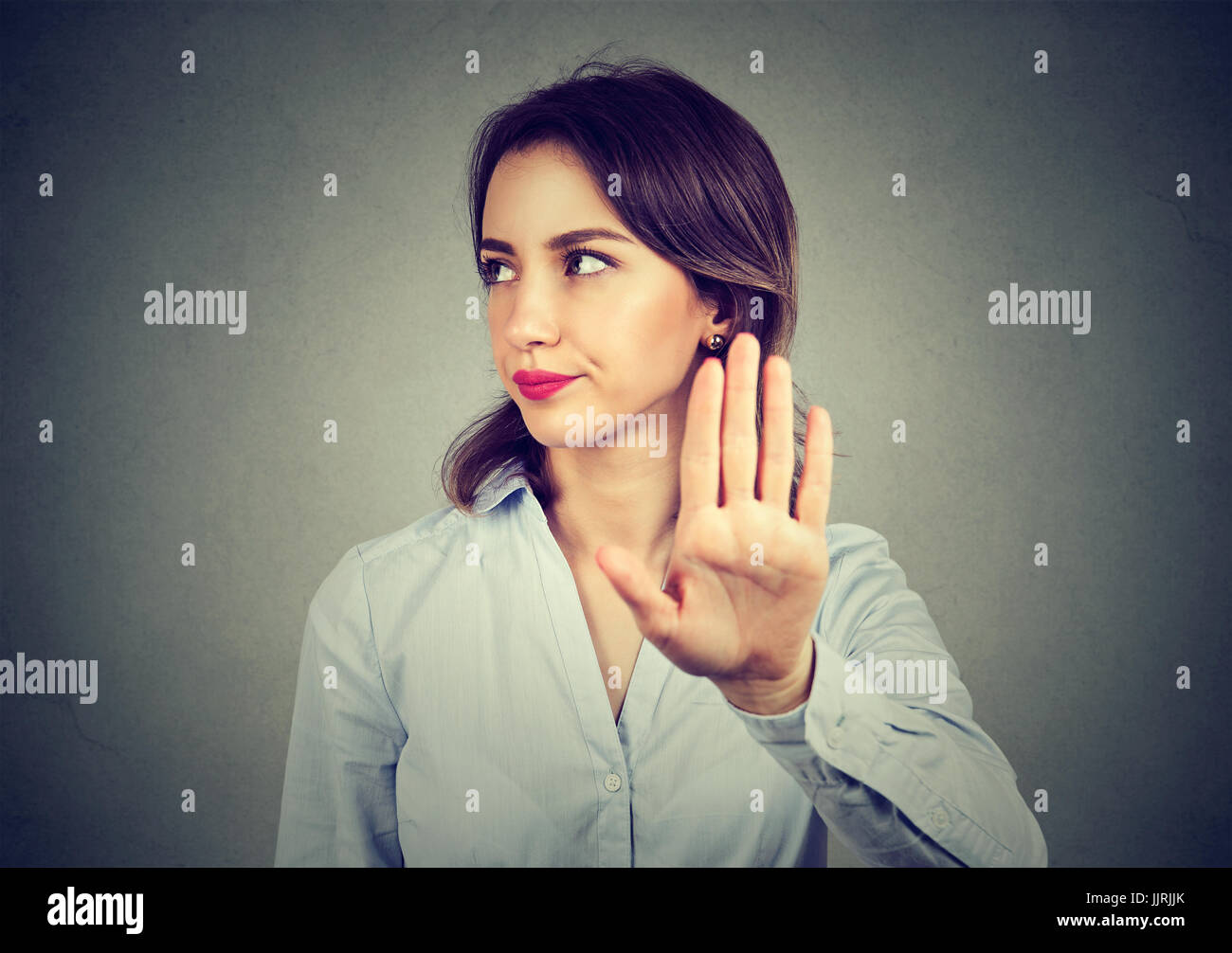 Angry woman giving talk to hand gesture with palm outward isolated gray wall background. Negative human emotion - Stock Image
