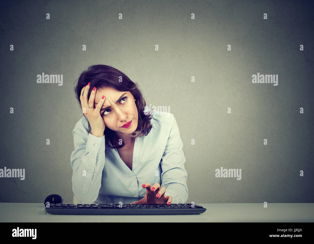 Desperate young woman trying to log into her computer forgot password - Stock Image