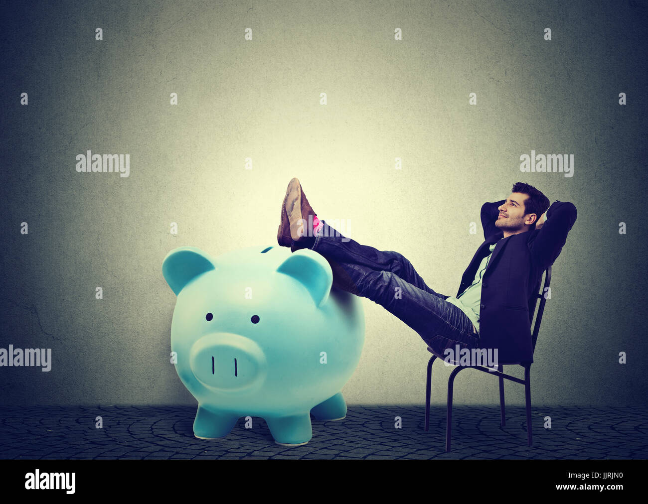 Financially successful business man sitting in chair and relaxing - Stock Image