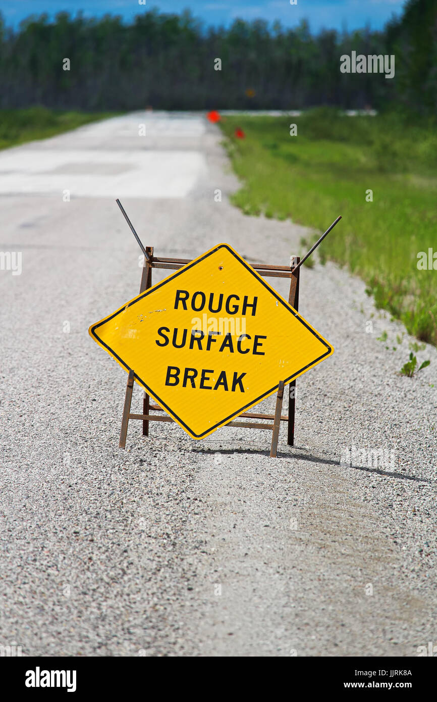 A yellow rough surface break sign with a road blurring into the background. - Stock Image