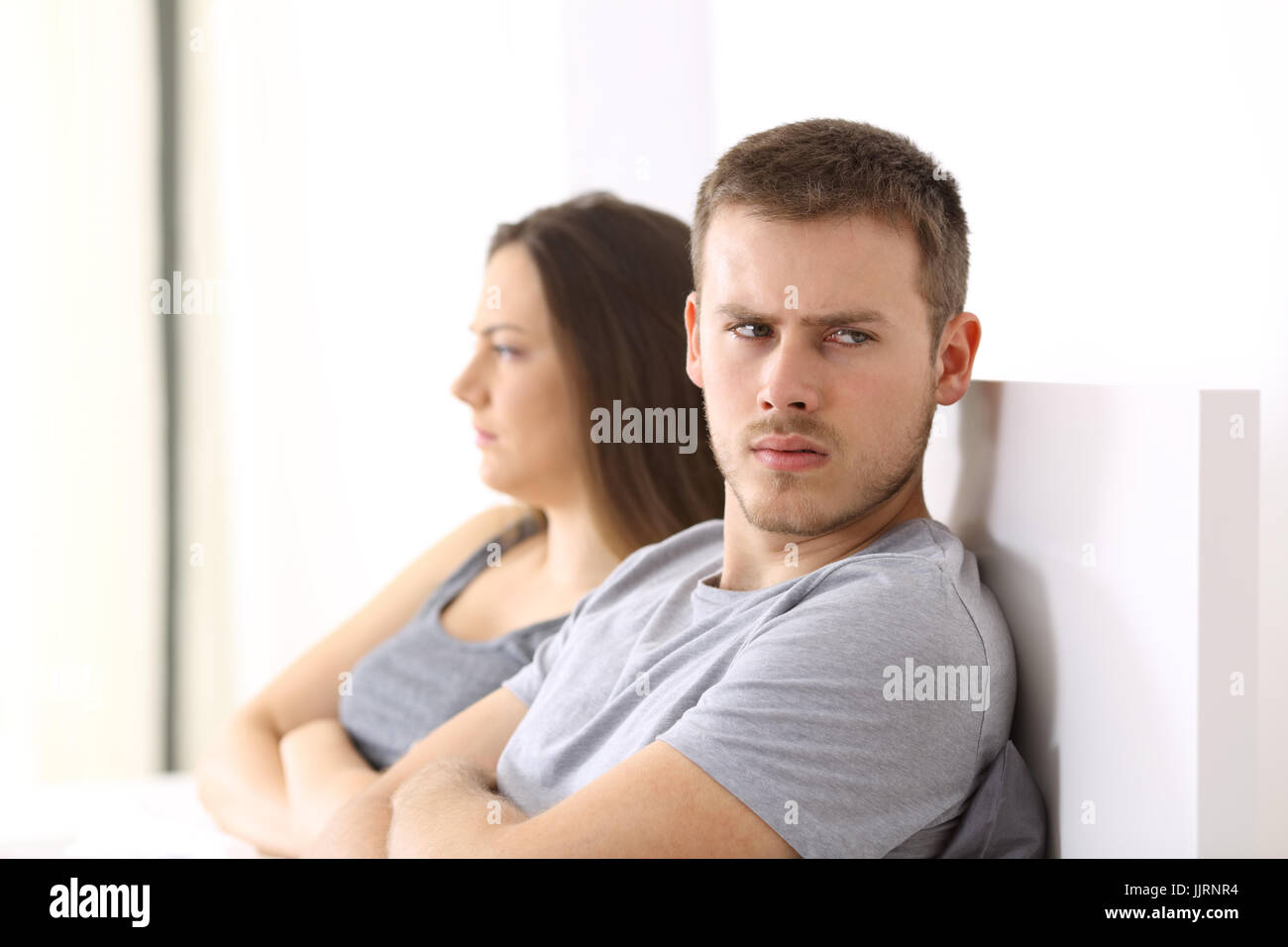 Angry couple after argument looking at another side sitting on the bed at home - Stock Image