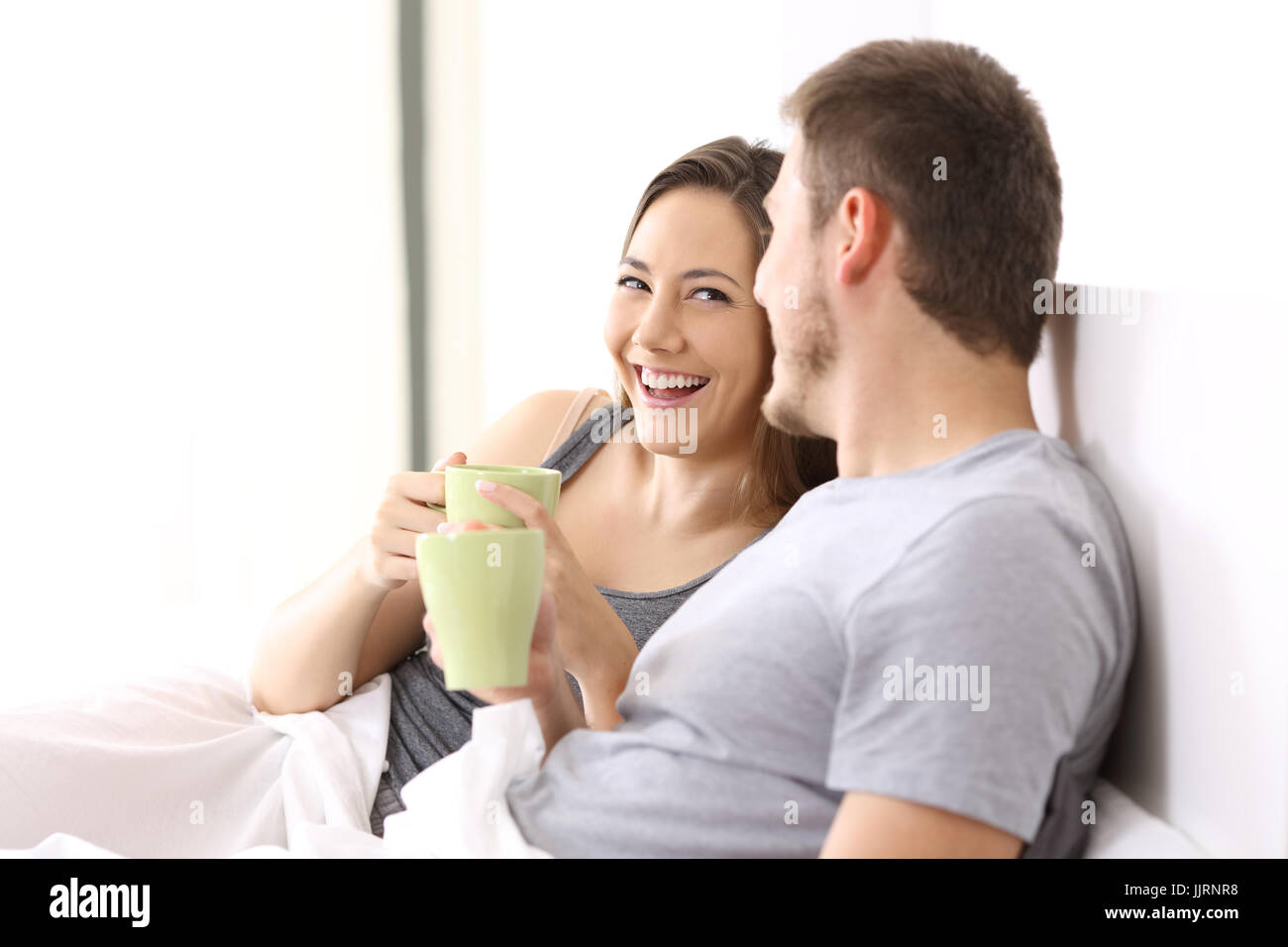 Happy couple having breakfast and talking on a bed of an hotel room or home - Stock Image