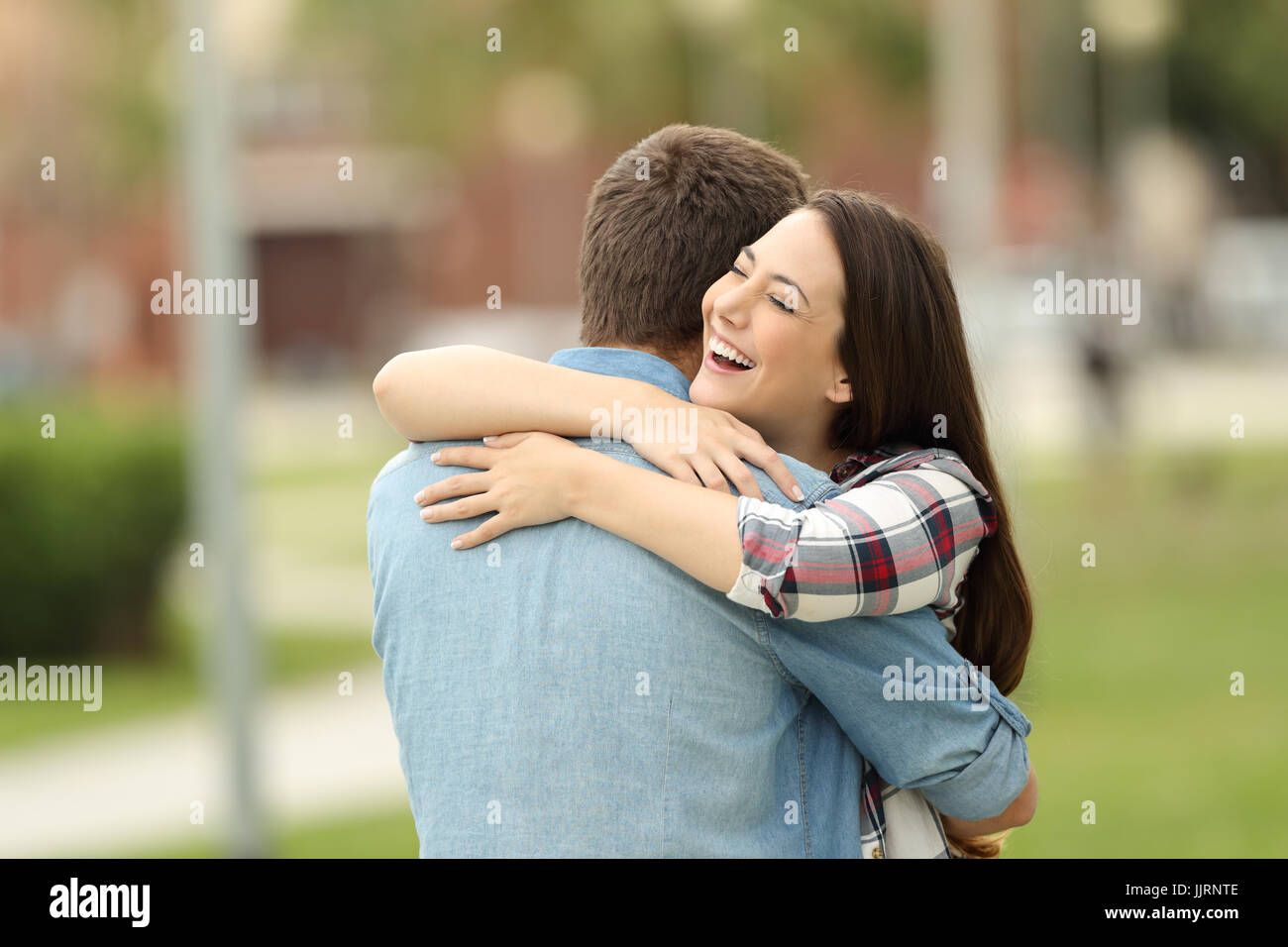 Happy encounter of two friends hugging outdoors in a park - Stock Image