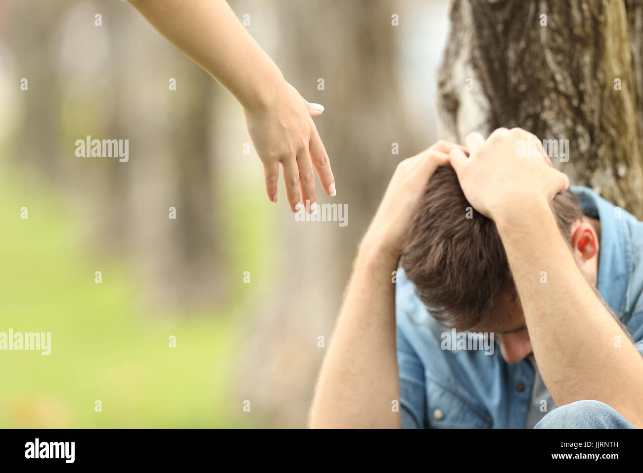 Sad teen sitting on the grass in a park and a woman hand offering help with a green background - Stock Image