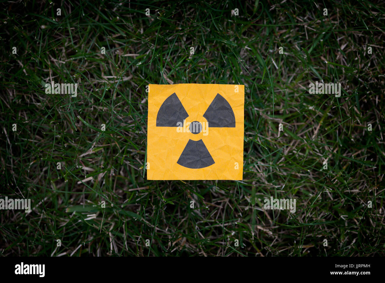 Radiation warning sign on a green grass. - Stock Image