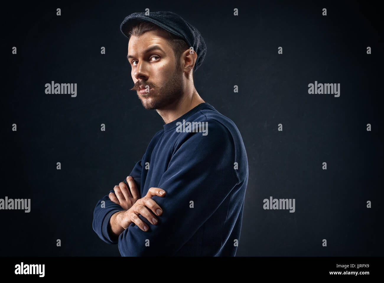 The young man in cap at studio - Stock Image