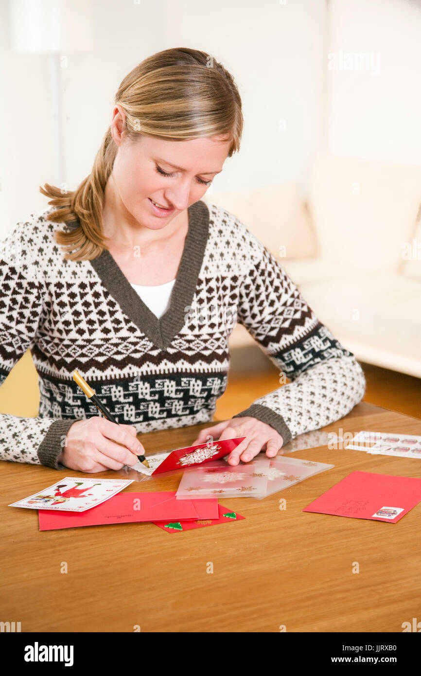 Woman writing christmas postcards Stock Photo