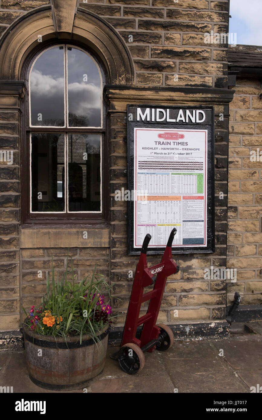 View of red porters' trolley by train times poster on platform at quaint, historic Oakworth Station - Keighley & Stock Photo