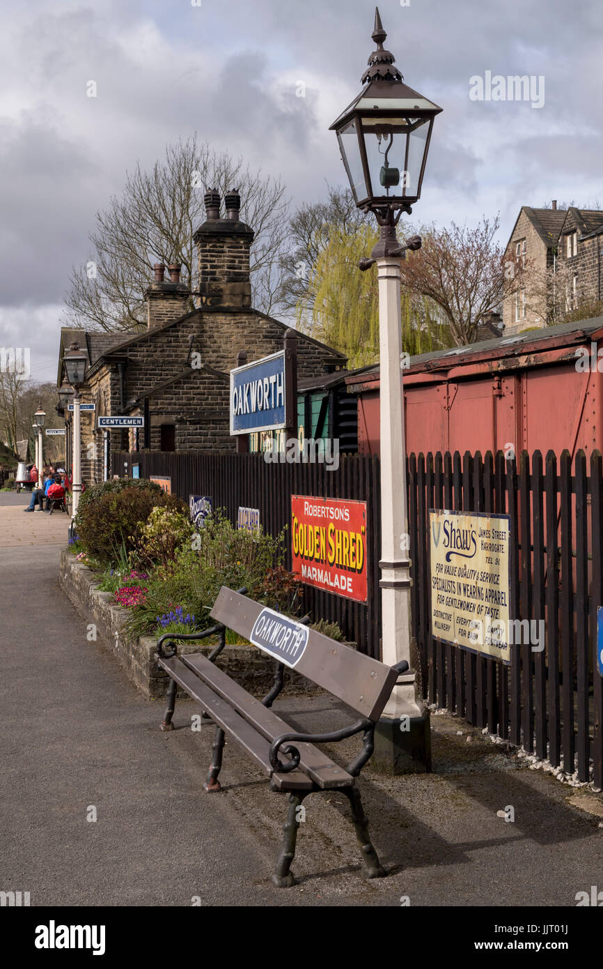 Looking along the quiet platform at quaint, historic Oakworth Station with gas lamps & retro adverts - Keighley - Stock Image