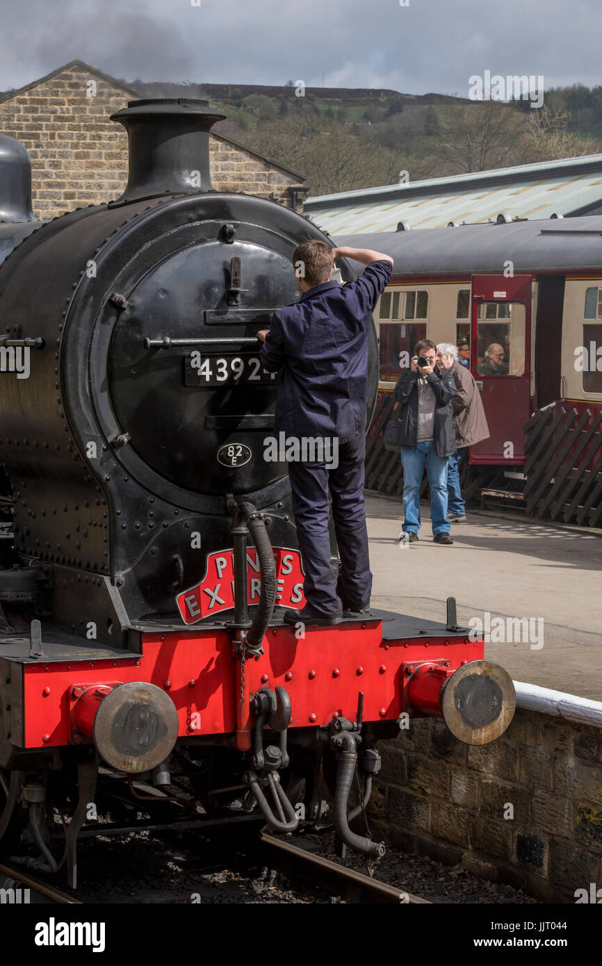 Train driver on front of steam locomotive, BR (Midland Railway) 4F 0-6-0 43924, stopped at station - Keighley and - Stock Image