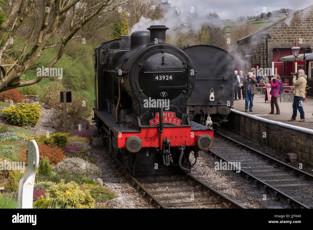 People view steam locomotive BR (Midland Railway) 4F 0-6-0 43924 pulling into station, puffing smoke - Keighley - Stock Image