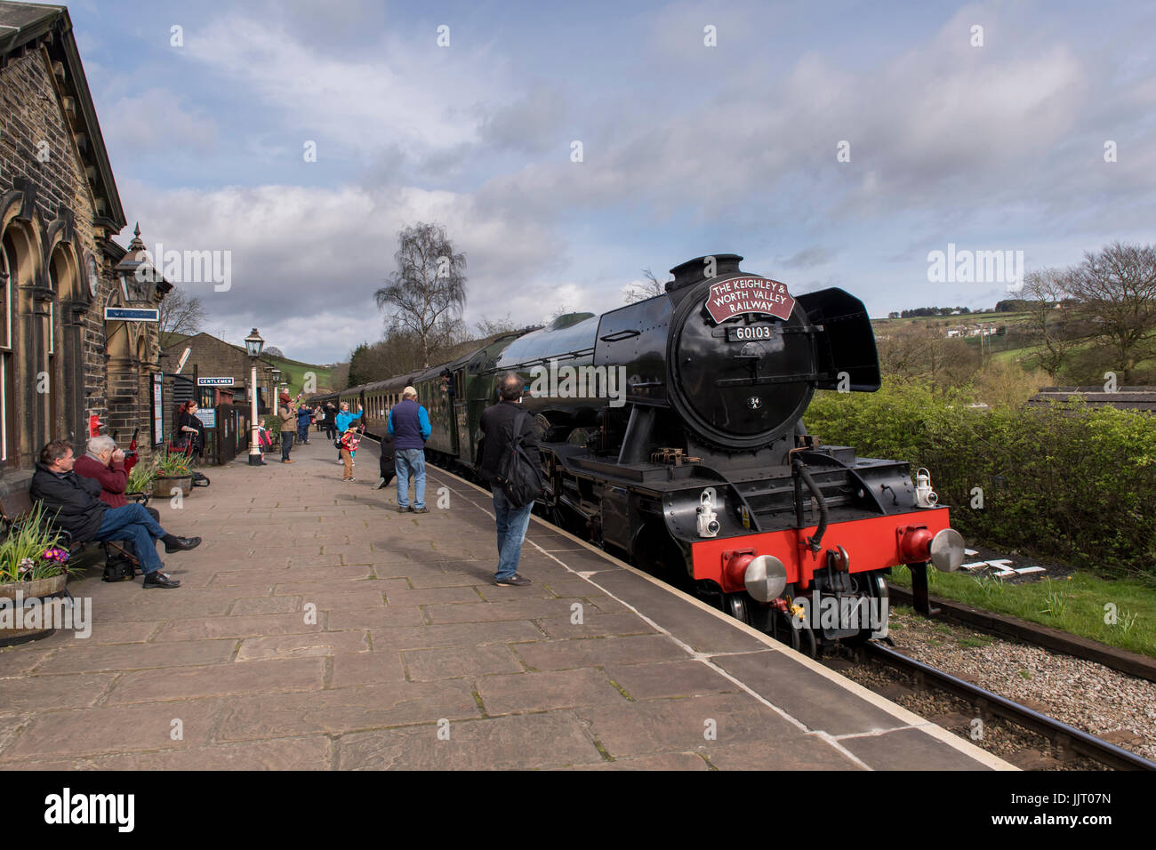 People on platform watch & wave at driver (iconic steam locomotive engine 60103 Flying Scotsman) at station - Keighley Stock Photo