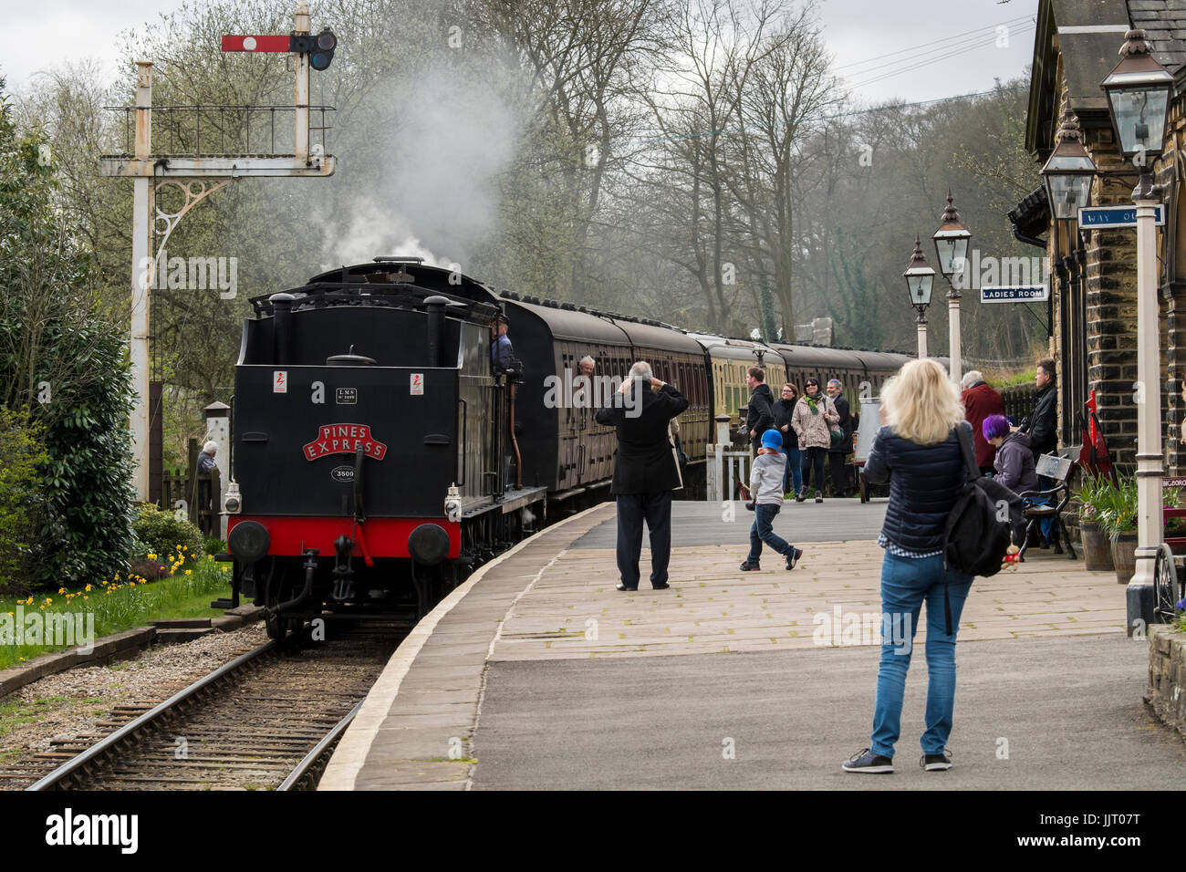 Steam locomotive, BR (Midland Railway) 4F 0-6-0 43924, leaving station, viewed by people on platform - Keighley - Stock Image