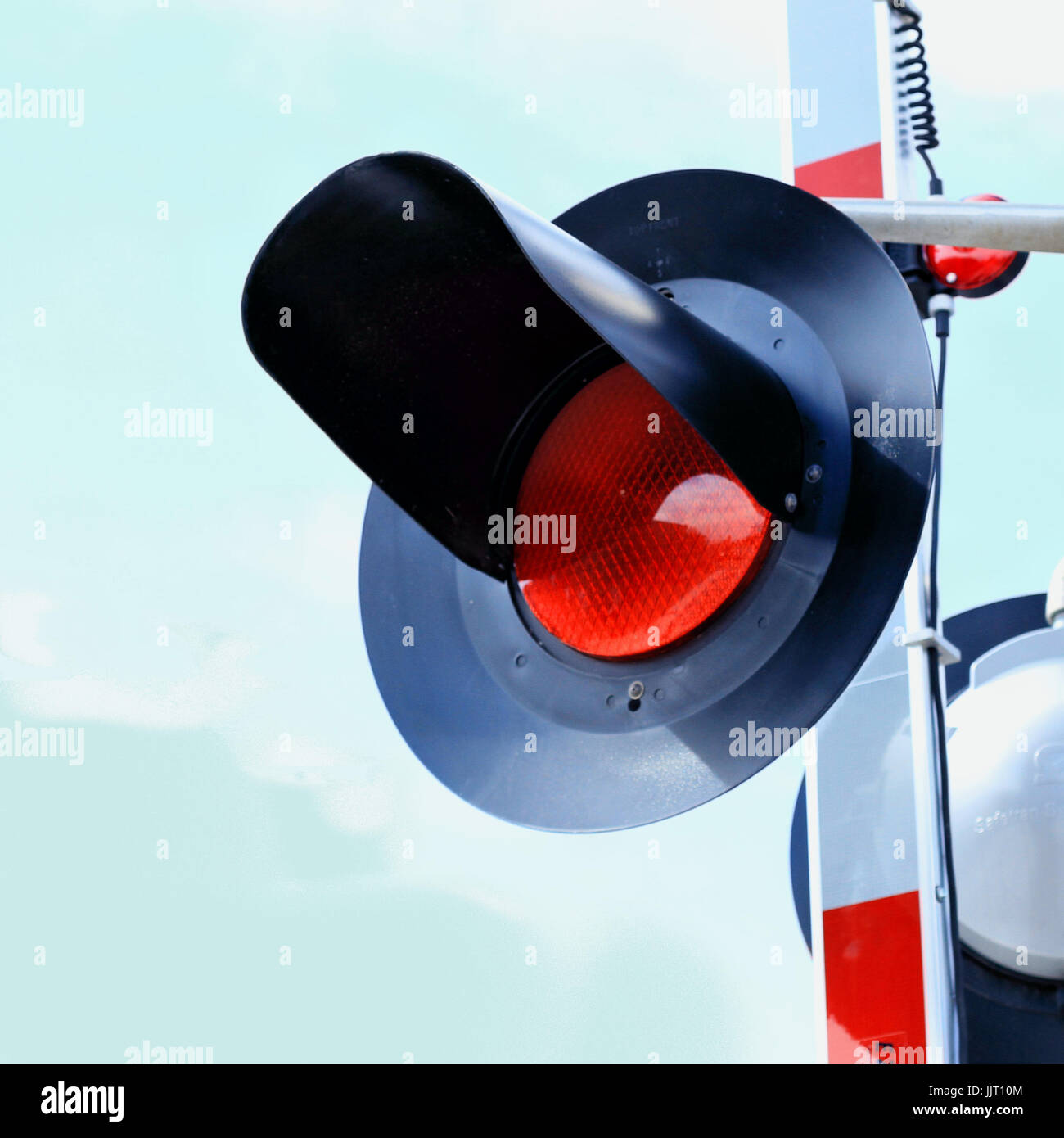 A railroad crossing light and arm stand at attention against a blue sky. - Stock Image